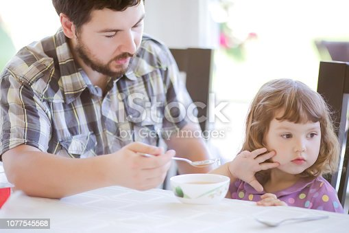 istock Cute little girl doesn't want to eat. Kid refusing food. Sad child. 1077545568