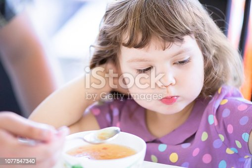 istock Cute little girl doesn't want to eat. Kid refusing food. Sad child. 1077547340