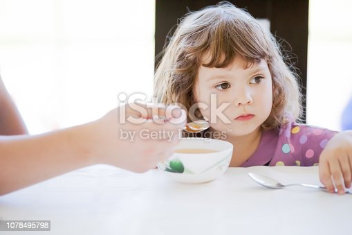 istock Cute little girl doesn't want to eat. Kid refusing food. Sad child 1078495798