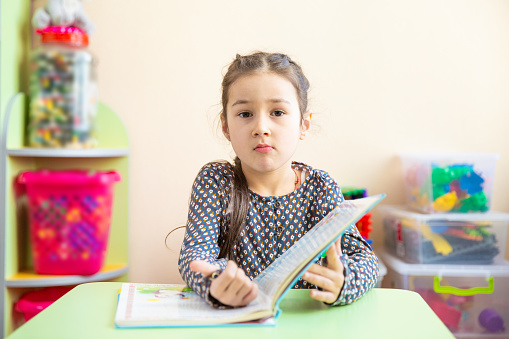1019302738 istock photo Cute little girl doing homework, reading a book, coloring pages, writing and painting. Children paint. Kids draw. Preschooler with books at home. Preschoolers learn to write and read. Creative toddler 948121078