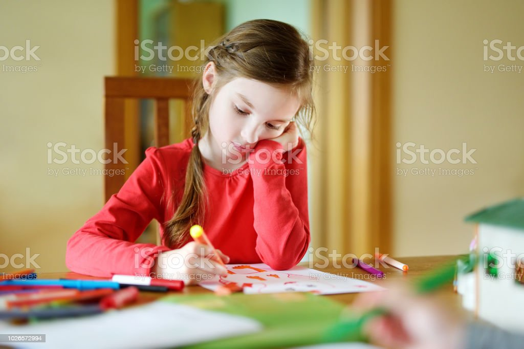 Cute little girl drawing a picture with colorful markers stock photo