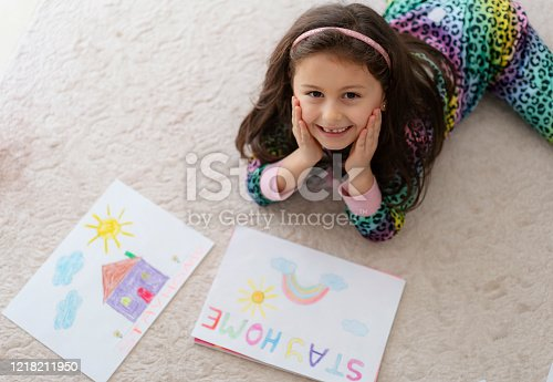 Cute little girl drawing pictures at home with a stay at home saying on the paper