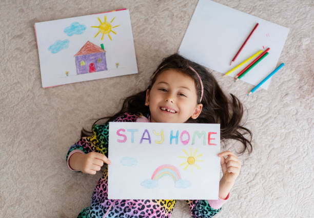 Cute little girl drawing pictures at home with a stay at home saying on the paper stock photo