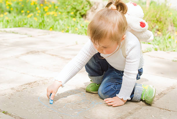 Cute little girl drawing with blue chalk outdoors stock photo