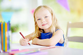 Cute little girl drawing with colorful pencils at a daycare. Creative kid painting at school. Girl doing homework at home.
