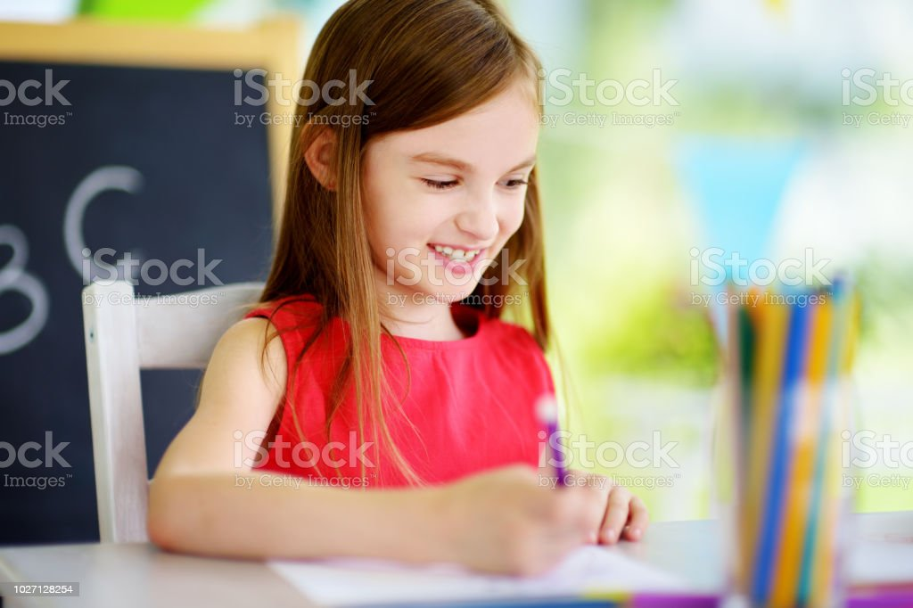Cute little girl drawing with colorful pencils at a daycare. Creative kid painting at school stock photo
