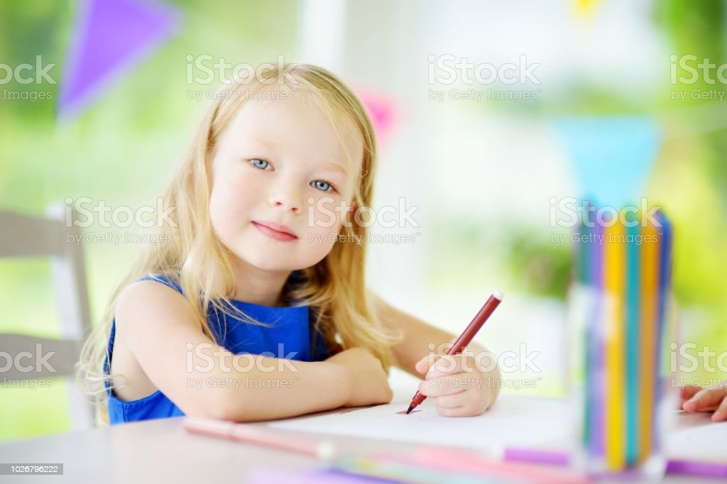 Cute little girl drawing with colorful pencils at a daycare stock photo