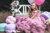 Cute little princess dressed in pink stunning dress surrounded French Macaron. Beautiful fashion girl sitting on a bench decorated with flowers and air balloons. Holiday or birthday party for your kids