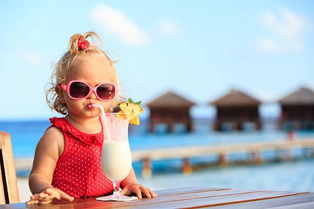 niedliche kleine mädchen trinkt cocktail auf tropischen strand - sonnenbrille kleinkind stock-fotos und bilder