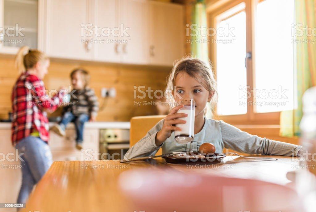 Niedliche kleine Mädchen trinken Milch beim Frühstück im Speisesaal. – Foto
