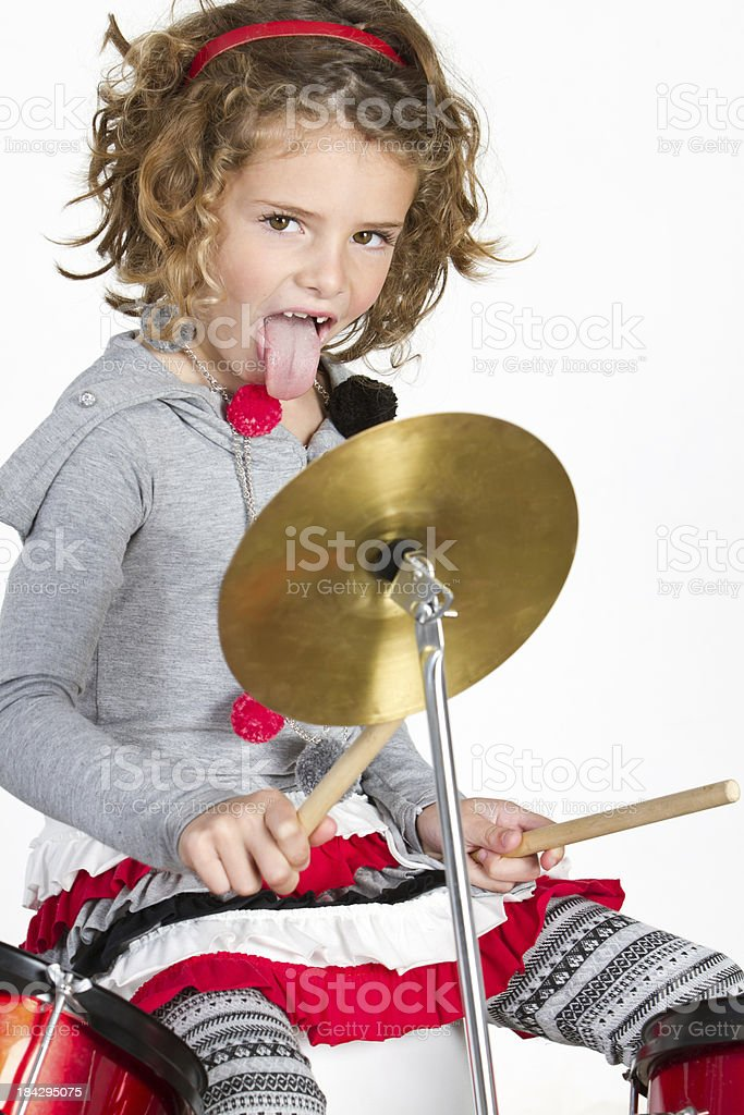 Cute little girl drumming and sticking out her tongue stock photo