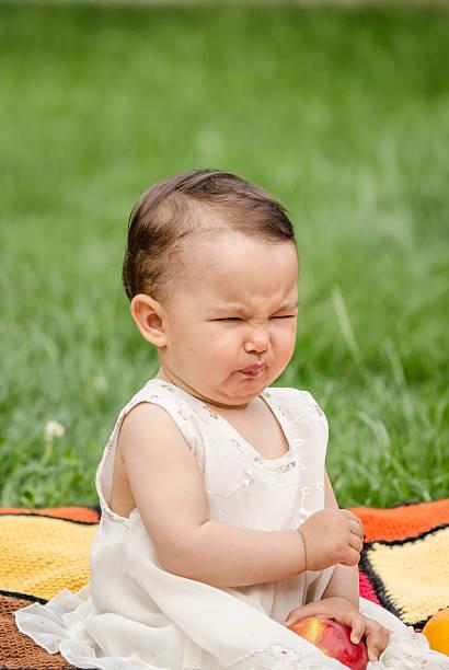 linda niña comiendo una manzana ácida - ácido fotografías e imágenes de stock