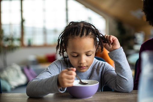 Cute little girl eating cereals for breakfast at dining table