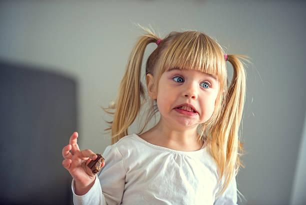 niedliche kleine mädchen essen schokolade - kinderschokolade stock-fotos und bilder