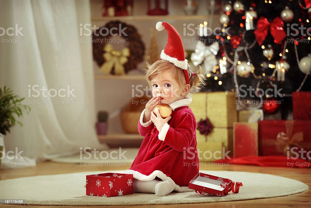 Cute little girl eating cookie secretly holding christmas bauble royalty-free stock photo