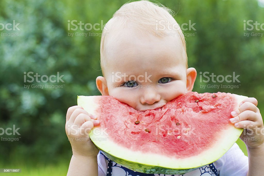 Cute little girl eating watermelon on the grass in summertime stock photo