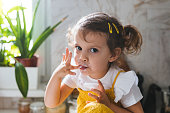 Portrait of cute Caucasian little girl eating whipped cream with her fingers and looking at camera.