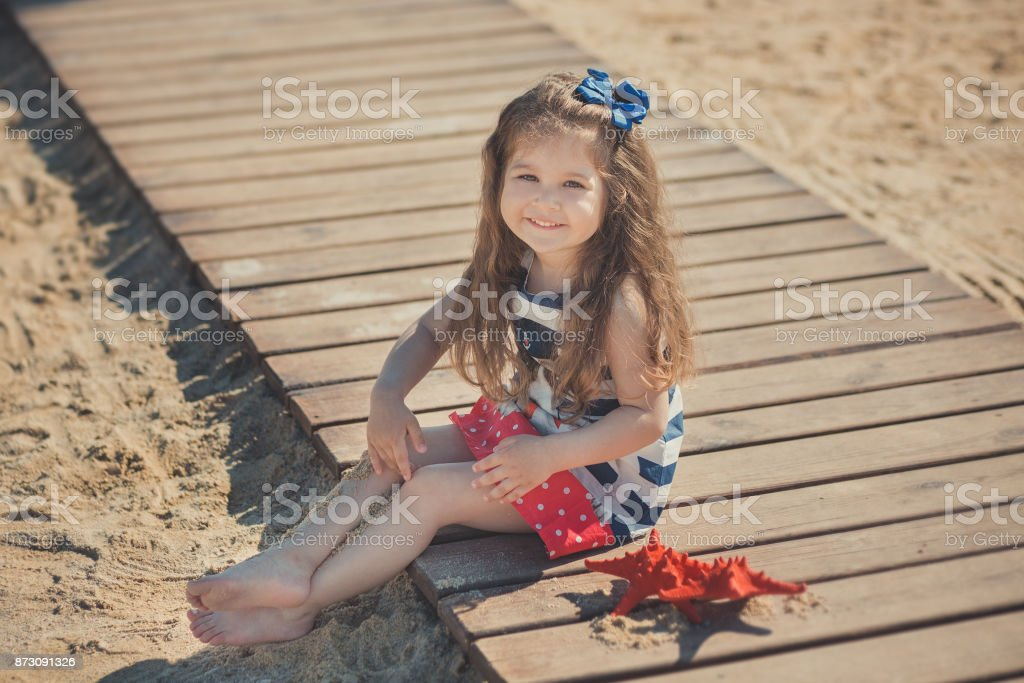 Cute little girl enjoying summer time on sea side beach happy playing with red star and tiny toy anchor on sand wearing nobby clothes with brunette hairs stock photo
