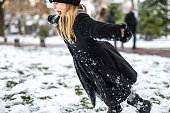 A little child plays with snow or pieces of ice outdoor in winter. A child activity in winter