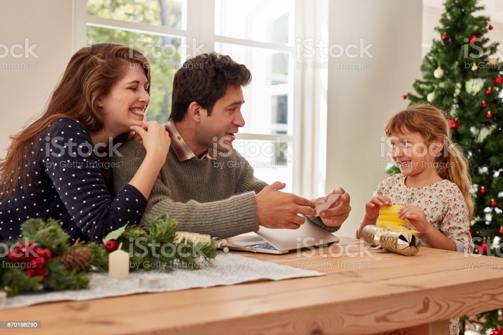 Cute little girl giving her christmas wish list to her parents. Happy...