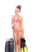 Portrait of cute little girl wearing bikini holding fins and luggage on white background