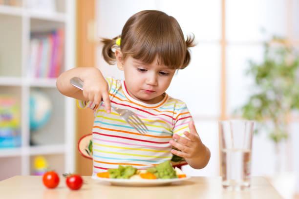 Cute little girl has a lunch in nursery stock photo