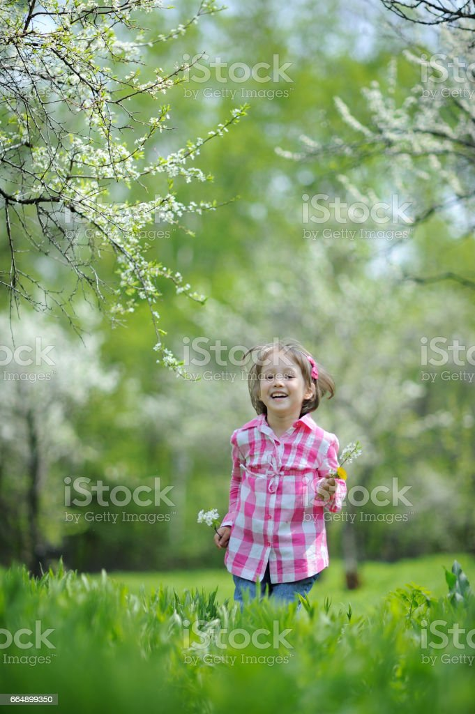 Cute little girl having fun in blooming cherry garden on beautiful  spring day foto stock royalty-free