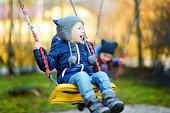 Cute little girl having fun on a swing on beautiful autumn day