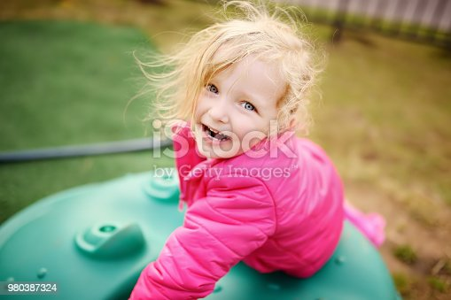 Cute little girl having fun on outdoor playground. Spring/summer/autumn active sport leisure for kids