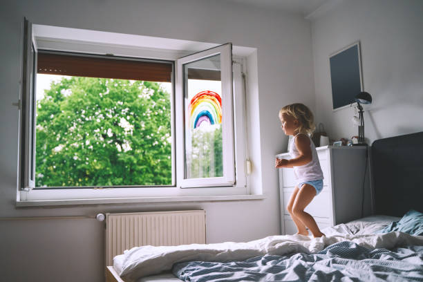 Cute little girl having fun time jumping on bed on background of window with a painted rainbow. Cute little girl having fun time jumping on bed on background of window with a painted rainbow. Kids leisure and play at home. Image of healthy and happy childhood, creativity, family, joy and fun. little girls in panties stock pictures, royalty-free photos & images