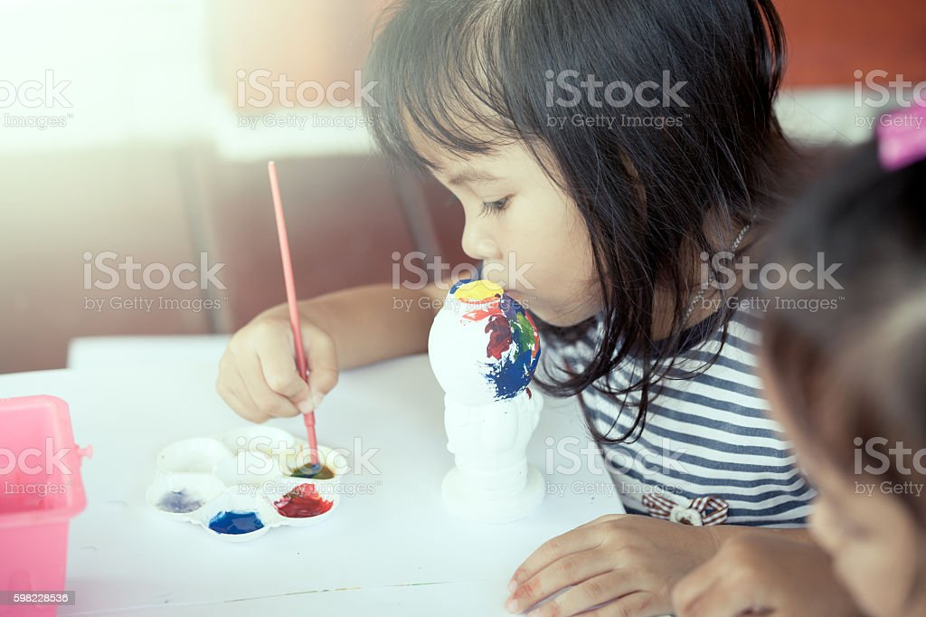 cute little girl having fun to paint on stucco doll foto royalty-free