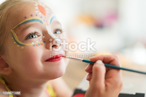 istock Cute little girl having her face painted for Halloween party. Halloween or carnival family lifestyle background. Face painting, headshot close up. 1038671488