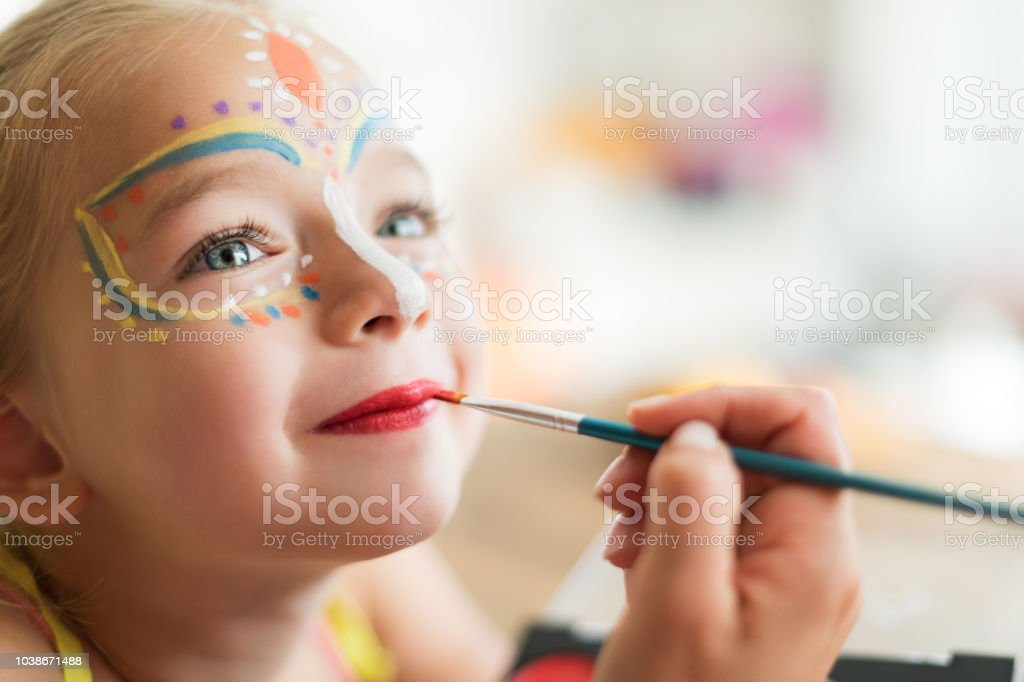 Cute little girl having her face painted for Halloween party. Halloween or carnival family lifestyle background. Face painting, headshot close up. stock photo
