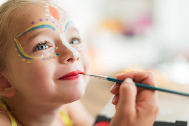 cute little girl having her face painted for halloween party. halloween or carnival family lifestyle background. face painting, headshot close up. - carnival stock photos and pictures