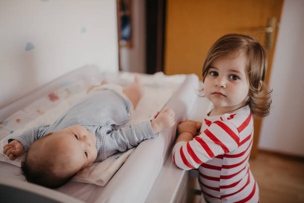 cute little girl helping granny change her brother's diapers - older brother imagens e fotografias de stock