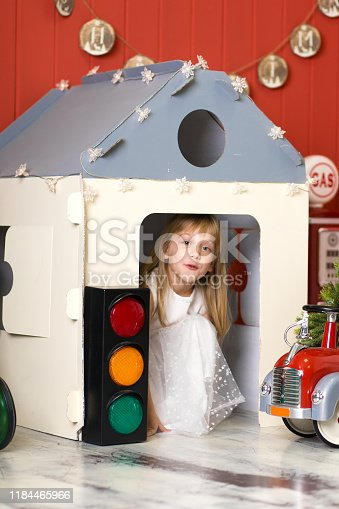 486524205 istock photo Cute little girl hiding in a cardboard house and playing with a big toy fire engine. Happy childhood. 1184465966