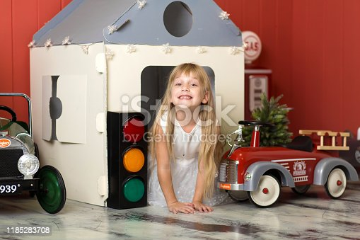 486524205 istock photo Cute little girl hiding in a cardboard house and playing with a big toy fire engine. Happy childhood 1185283708