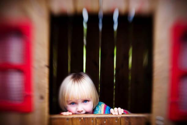 süßes kleines mädchen im haus verstecken spielen - mädchen spielhaus stock-fotos und bilder