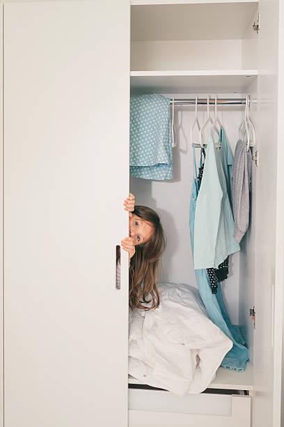 cute little girl hiding in wardrobe - mutterkleiderschrank stock-fotos und bilder