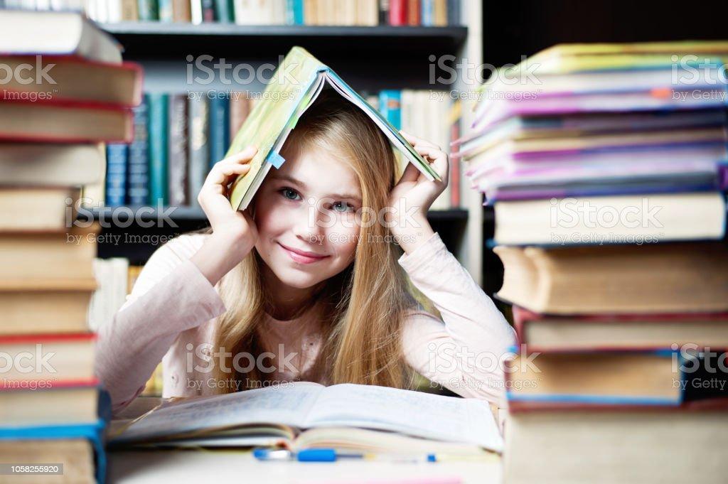 Niedliche kleine Mädchen versteckt unter buchen in der Nähe von Stapel Bücher – Foto