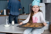 cute little girl holding a baking sheet of cookies