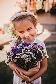 Cute Little girl holding purple flowers for her mother