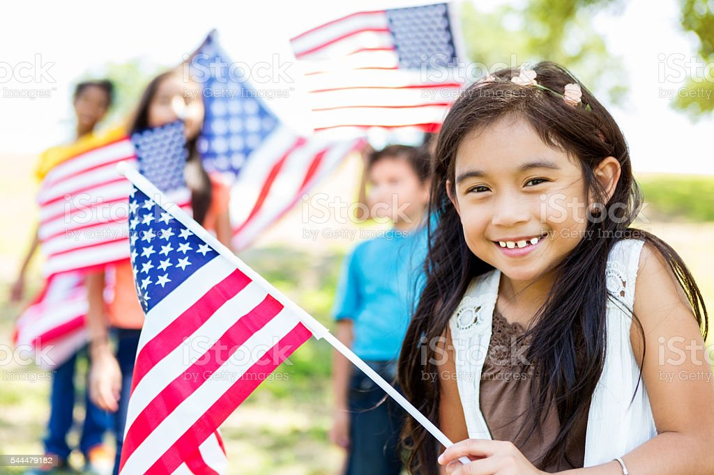 Cute little girl holds American Flag Adorable elementary age Hispanic little girl smiles and giggles as she waves an American flag at Independence Day parade or party. Her friends are behind her also waving flags. Agricultural Field Stock Photo