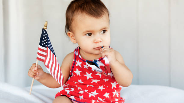 Cute little girl holds an American flag in hand  and celebrate Independence Day on 4th of July stock photo