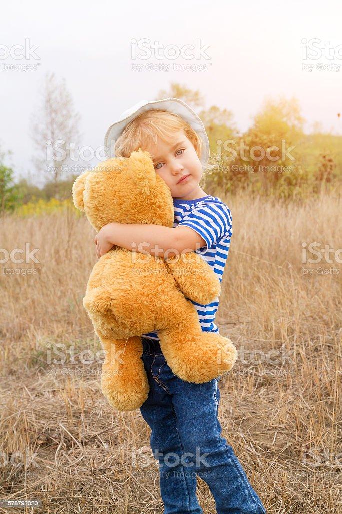 Cute little girl standing in the grass hugging a Teddy bear