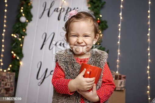 579124316 istock photo Cute little girl in a red blouse with a cup of tea in her hands laughing joyfully against the background of Christmas illumination 1186378259
