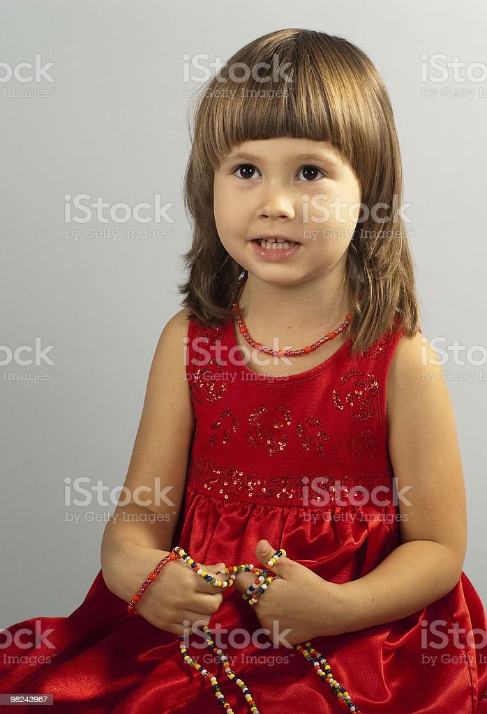 Cute little girl in a red dress with necklace royalty-free stock photo