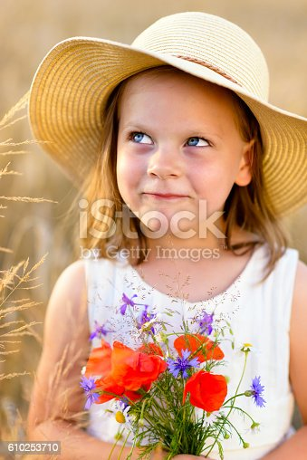 dfb46ff859f istock Cute little girl in a straw hat with wild flowers 610253710