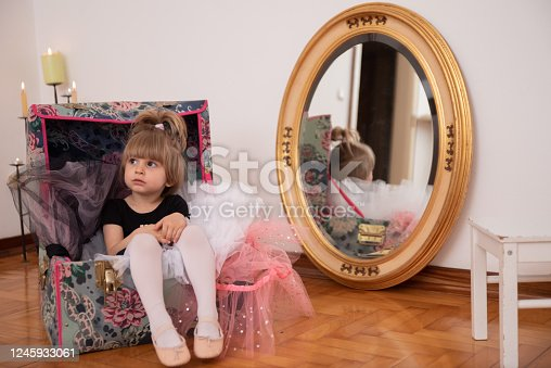 Cute Little Girl In Ballerina Dress Sitting in Trunk Between Multicolored Tulle Skirts