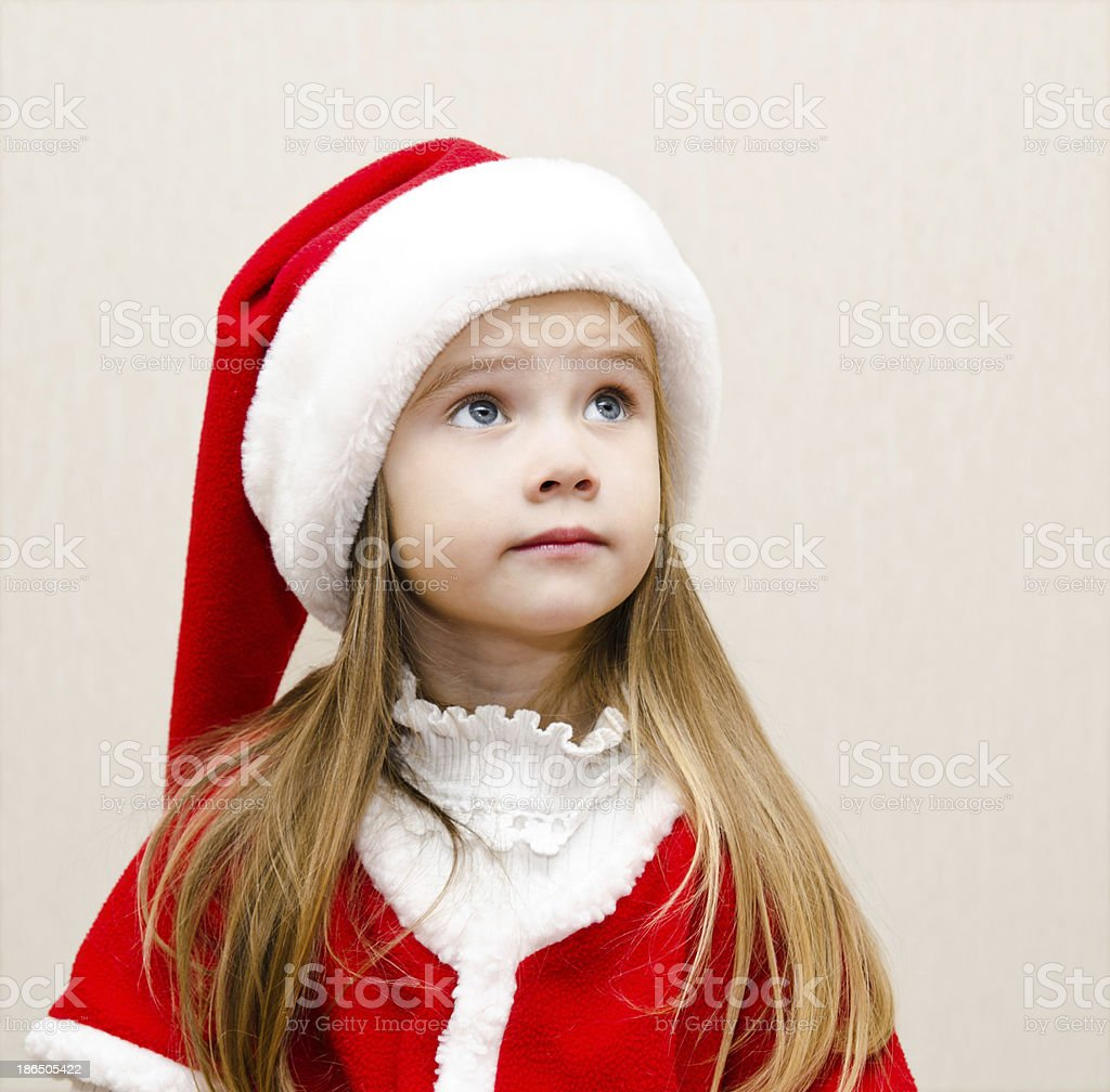 Cute little girl in christmas hat dreaming and looking up royalty-free stock photo